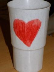 Flora fotópályázat nyertes képe, egy műanyag pohár, rajta egy zsírkrétával rajzolt szívecske, undorító kivitelezésben.