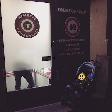 Kisbaba babakocsiban egy Nemzeti Dohánybolt előtt